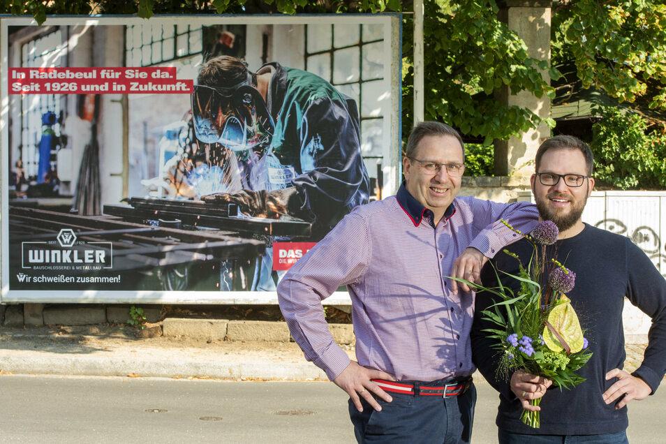 Michael (links) und Markus Winkler vor dem Werbeplakat für ihre Firma an der Ecke Moritzburger Straße, Karlstraße.