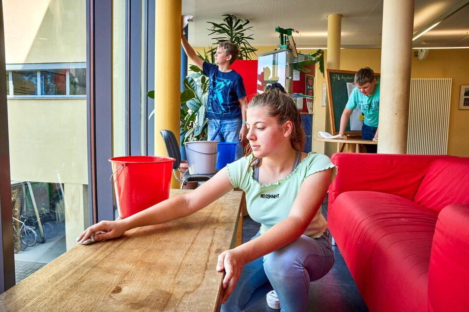 Putzaktion in der letzten Schulwoche: Jaron, Tabea und Tim (v.l.) aus der achten Klasse wischen Tische und Säulen im Pirnaer Herder-Gymnasium ab.