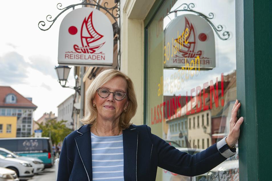 """Evi Klotzsche-Bieler vom gleichnamigen Großenhainer Reisebüro vor ihrem Geschäft: """"30 Jahre alles gegeben. Lasst uns leben!"""" steht inzwischen auf dem Schaufenster."""