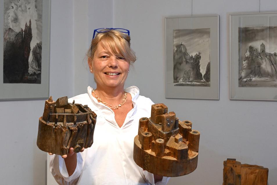 Museumsleiterin Daniela Simon mit hölzernen Burgen von Armin Münch, links Rabenau, rechts Frauenstein.