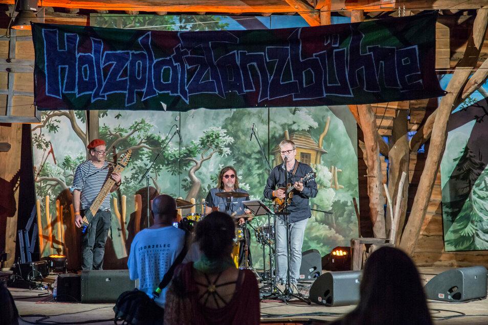 """Viele Bühnen wie die Holzplatztanzbühne - hier mit der Band """"Watering Eye"""" - waren mit Bretterwänden gegen den Durchgangsverkehr abgegrenzt. Insgesamt traten über 500 Künstler zum Folklorum auf."""
