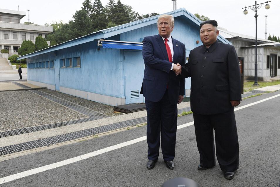 US-Präsident Donald Trump (l) und Nordkoreas Machthaber Kim Jong Un geben sich im Grenzdorf Panmunjom in der entmilitarisierten Zone (DMZ) die Hand.