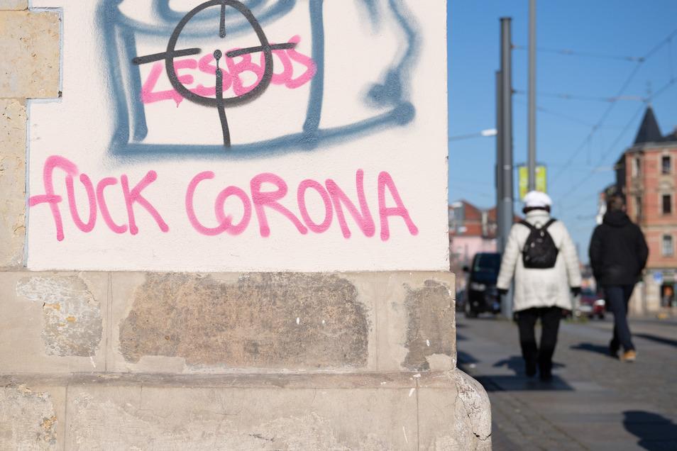 """Passanten gehen in Dresden an einem Graffito mit der Aufschrift """"Fuck Corona"""" vorbei."""