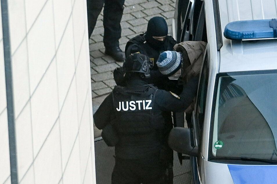 Der Angeklagte Stephan Balliet (r) wird bei seiner Ankunft am Landgericht Magdeburg von Justizpersonal aus dem Fahrzeug begleitet.