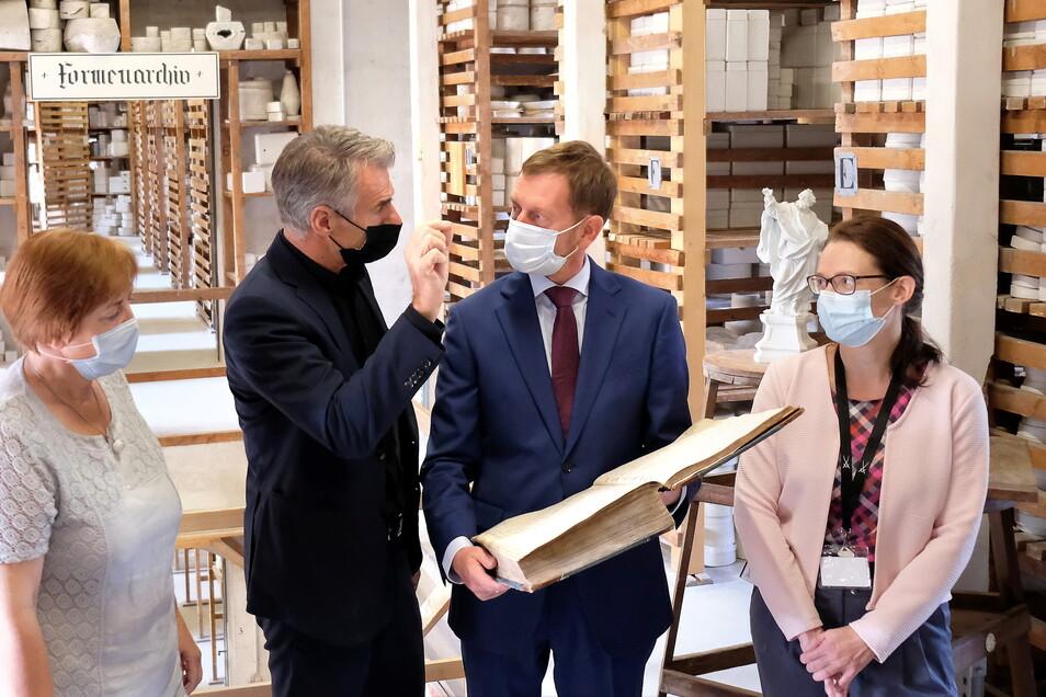 Im historischen Buch in der Hand des Ministerpräsidenten ist verzeichnet, in welchem Gang die verschiedenen Formen für Tisch- und Tafelservice zu finden waren. Insgesamt lagern 700.000 Formen im Archiv. Daneben Geschäftsführer Tillmann Blaschke.