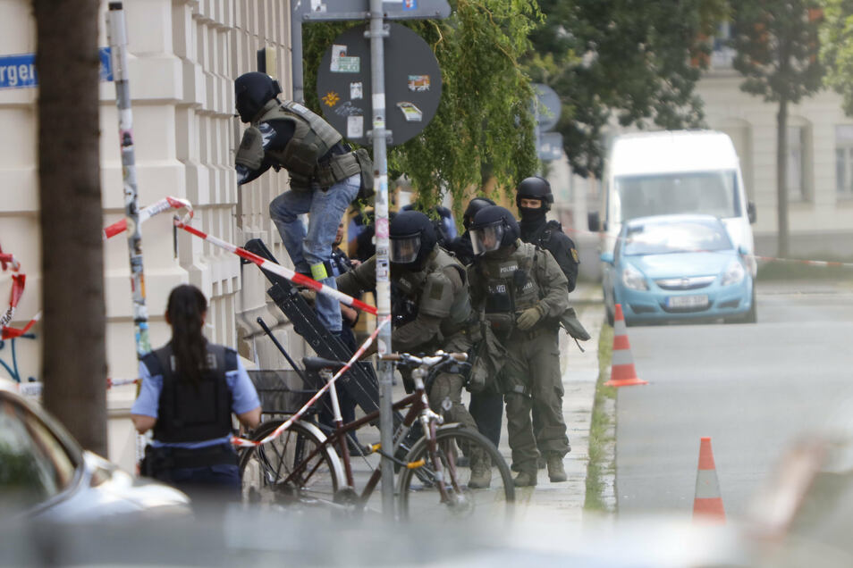 Polizisten stehen während des SEK-Einsatzes vor dem Wohnhaus des aggressiven Mieters.