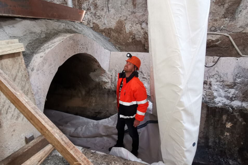 Bauleiter Martin Lehmann inspiziert in der Baugrube, wie der erste Schlauch in die zwei Meter hohe Betonröhre kommt.