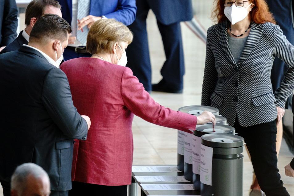 Bundeskanzlerin Angela Merkel (CDU) gibt ihre Stimmkarten bei der Abstimmung über Änderungsanträge bei der Sitzung des Bundestags ab.