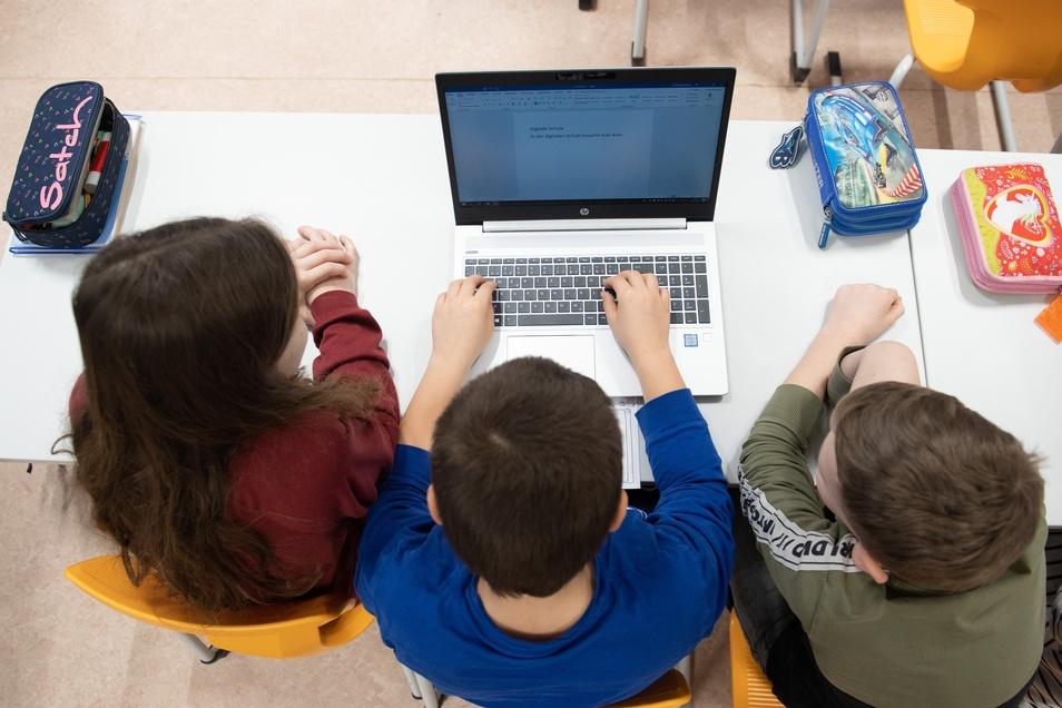 Drei Schüler teilen sich einen Laptop: Solche Zustände könnten sich künftig bessern.