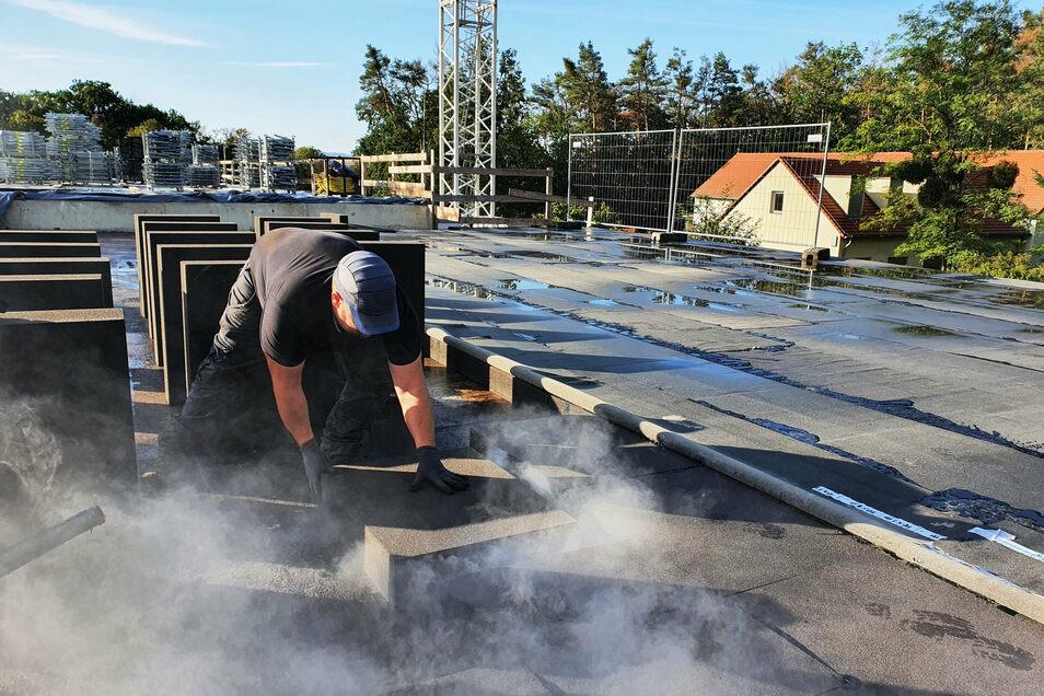 Auf dem Dach der Wasserkammer verlegt Sebastian von Nordheim Schaumglasplatten auf den frisch aufgebrachten heißen Bitumen.