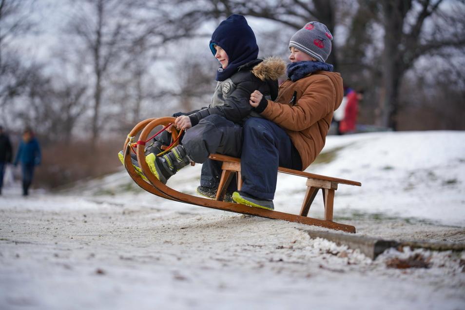 Davos und Thies fahren im Alaunpark Schlitten.