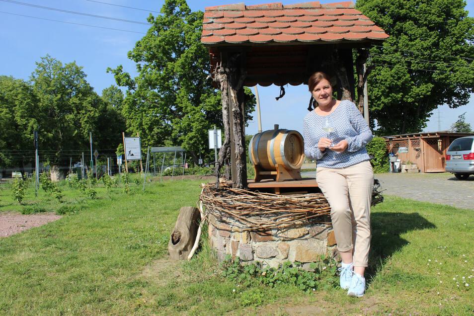 Katharina Lai am Brunnen ihrer kleinen Weinwirtschaft am Fuße des Seußlitzer Schlosses.