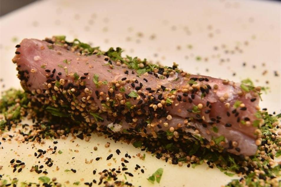 Ein Schweinefilet hüllt sich in gerösteten Schwarzkümmel und Senfsaat. Gleich kommt die Rolle ins heiße Wasser.