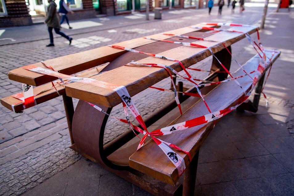 Corona-Schutzmaßnahme: Absperrband um einen Tisch vor einem Imbiss. Wenn am Montag in Sachsen kleinere Geschäfte und die Baumärkte öffnen dürfen, müssen Restaurants noch geschlossen bleiben.