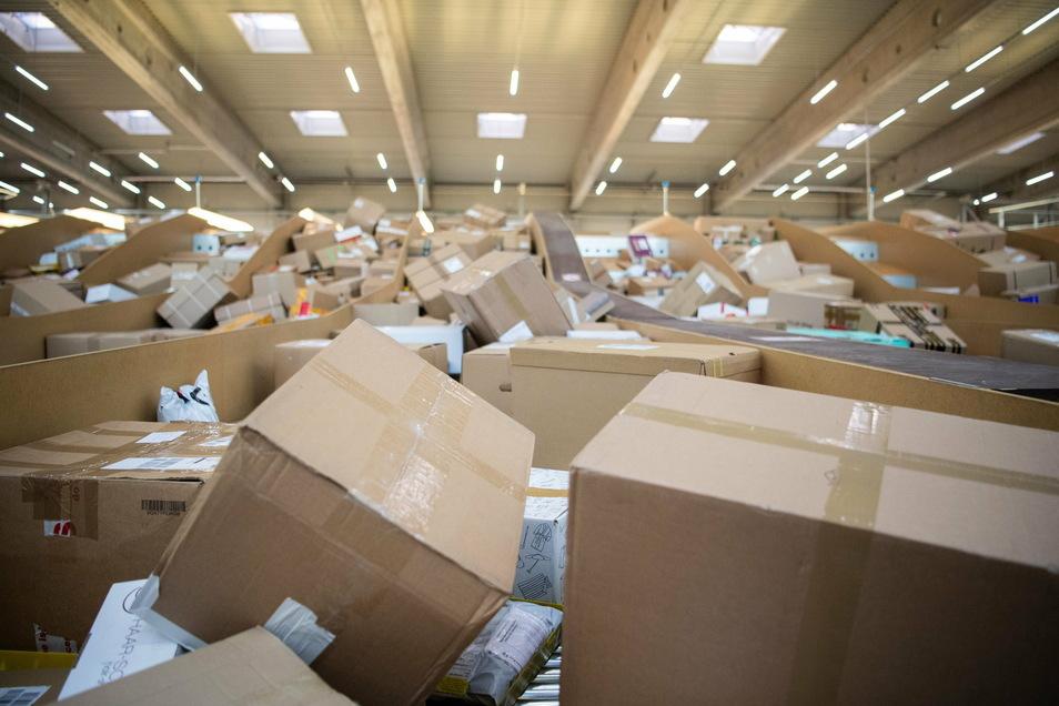 Pakete liegen in einem Paketzentrum von DHL.