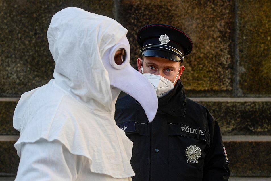 Ein Polizist beobachtet in Prag einen Teilnehmer einer Demonstration gegen die Corona-Masssnahmen.