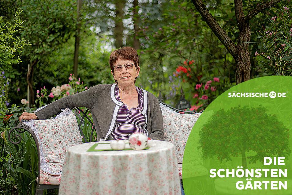 Als würde man im Wald sitzen: Hannelore Knöfel macht es sich auf einer Bank in ihrem Garten in Großröhrsdorf bequem. Hinter ihr rauschen die Bäume.