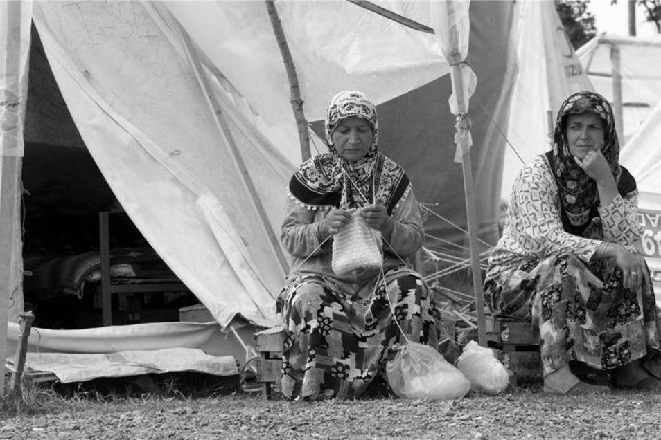 Gut einem Monat nach dem schweren Erdbeben von Gölcük im August 1999, bei dem mehr als 17.000 Menschen ums Leben kamen, sitzen obdachlos gewordene Frauen vor provisorischen Zelten am Stadtrand von Izmit.