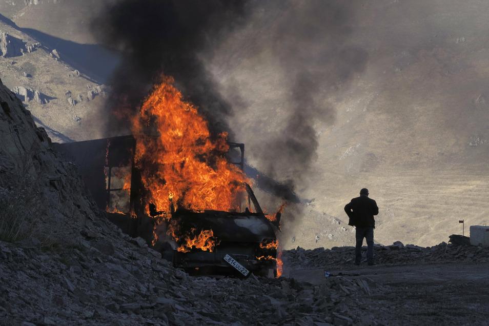 Ein Mann steht in der Nähe seines brennenden Autos, das beim Aufstieg entlang der Straße zu einem Bergpass nahe der Grenze zwischen Berg-Karabach und Armenien in Brand geraten ist.