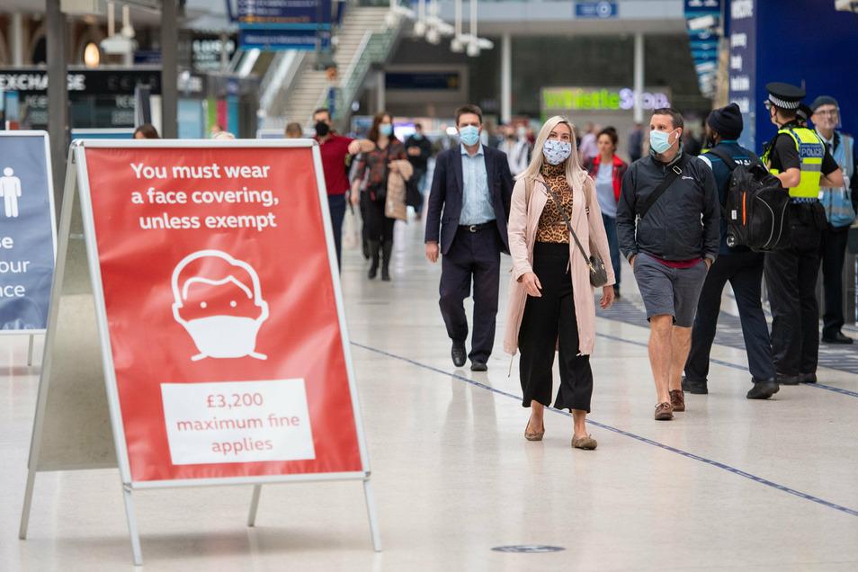 Pendler gehen im Londoner Bahnhof Waterloo. In Großbritannien gelten angesichts stark steigender Corona-Zahlen wieder schärfere Schutzmaßnahmen.
