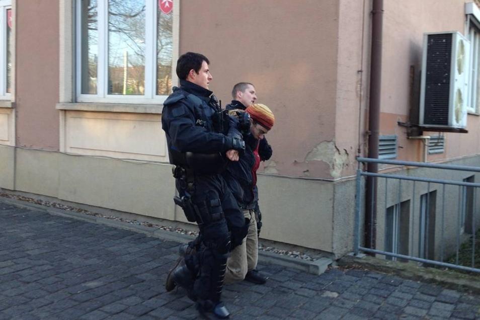 Polizisten führen einen Gegner der Räumung ab.