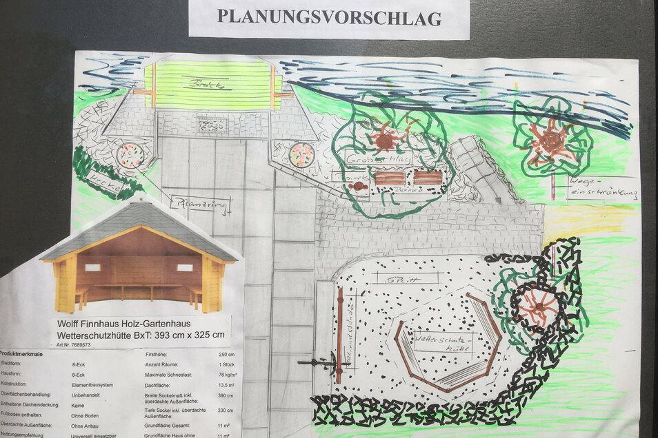 Dieser Plan an einer Scheune zeigt, wie der Platz an der Brücke mal aussehen soll: mit Wetterschutzhütte, Fahrradständer und neuer Bepflanzung.