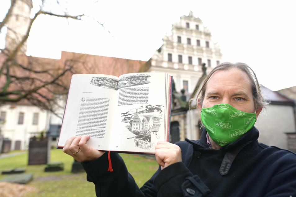 Peter Knüvener mit der Hefftergiebel-Illustration aus dem Grimm'schen Märchenbuch vor der realen Sehenswürdigkeit.