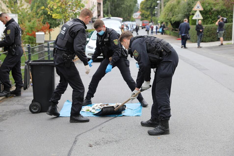 Polizisten durchsuchten am Donnerstagvormittag in Großröhrsdorf den Inhalt von Mülltonnen.
