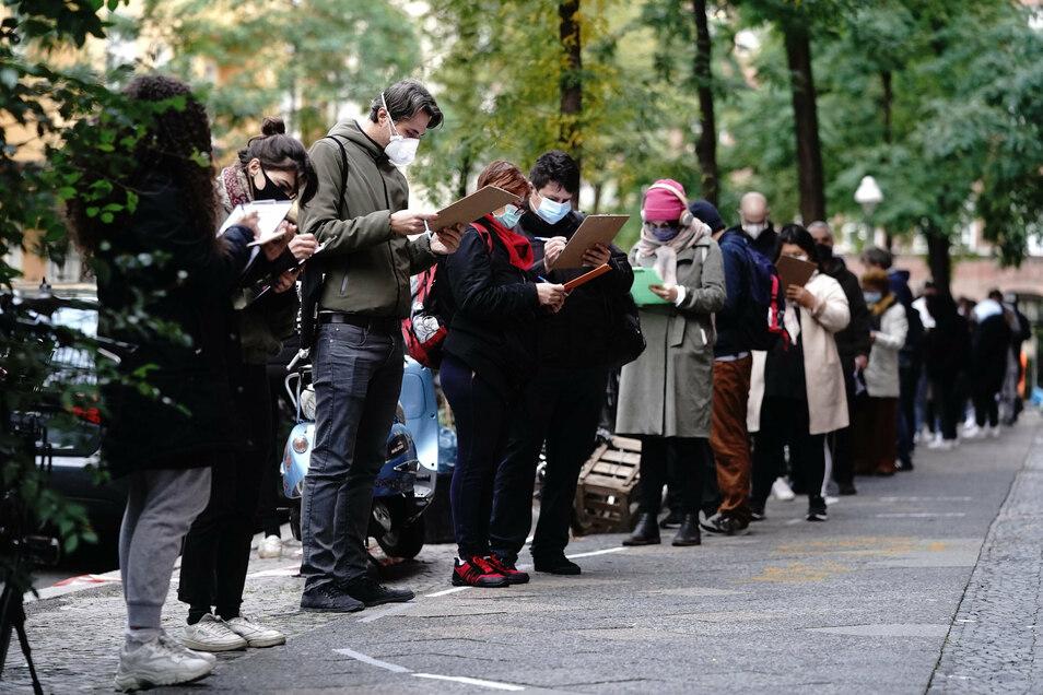 Menschen mit Nasen- und Mundschutz stehen in einer langen Schlange vor einer Arztpraxis im Bezirk Neukölln für einen Corona-Test an.