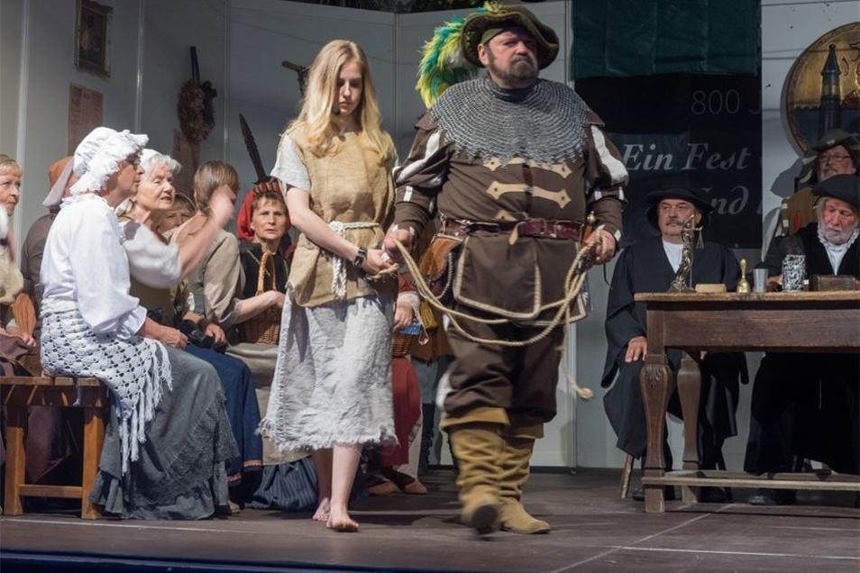 Magd Anna, gespielt von Fanny Major, wird dem Gericht vorgeführt. Die dramatische Geschichte fußt auf einer wahren Begebenheit, die sich laut Chronik um 1500 in Stolpen ereignete.