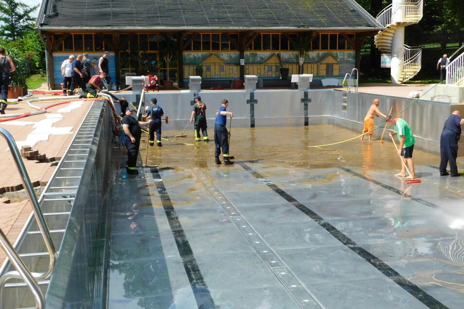 """Freiwillige Helfer und Kameraden der Feuerwehr reinigten einen Tag nach den Überschwemmungen das Freibad """"Wasserwelt"""" in Steinigtwolmsdorf."""