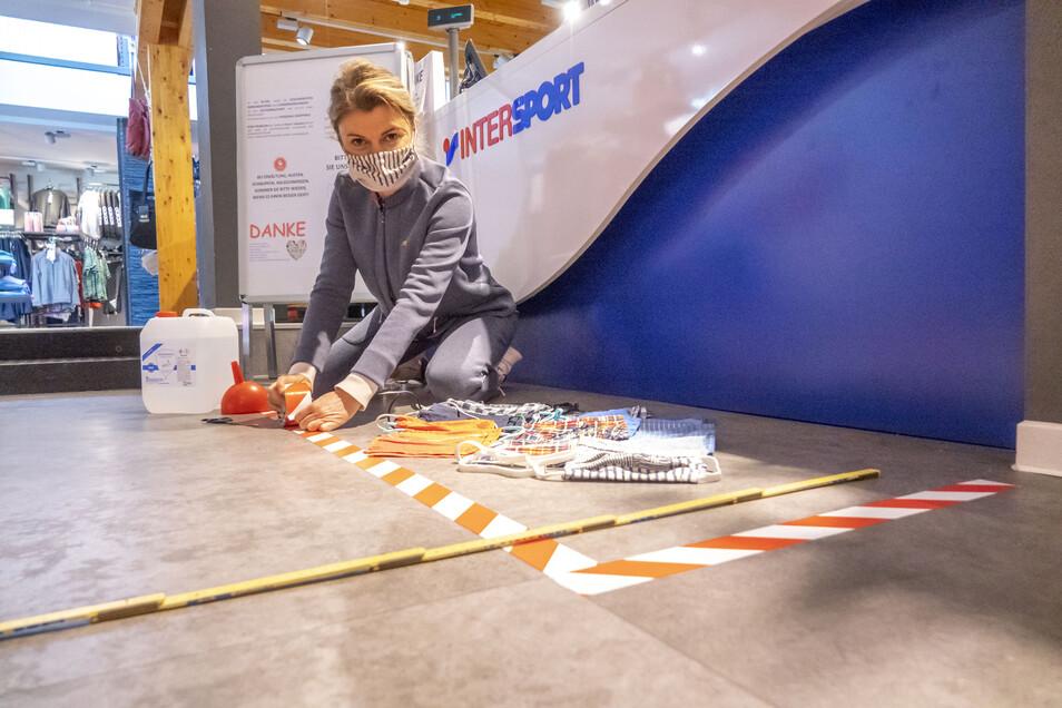 Wartelinien für die Kunden, Desinfektionsmittel und Schutzwand für die Mitarbeiter: Sylvia Donat von Intersport Donat in Riesa bereitet das Geschäft auf die Öffnung vor.