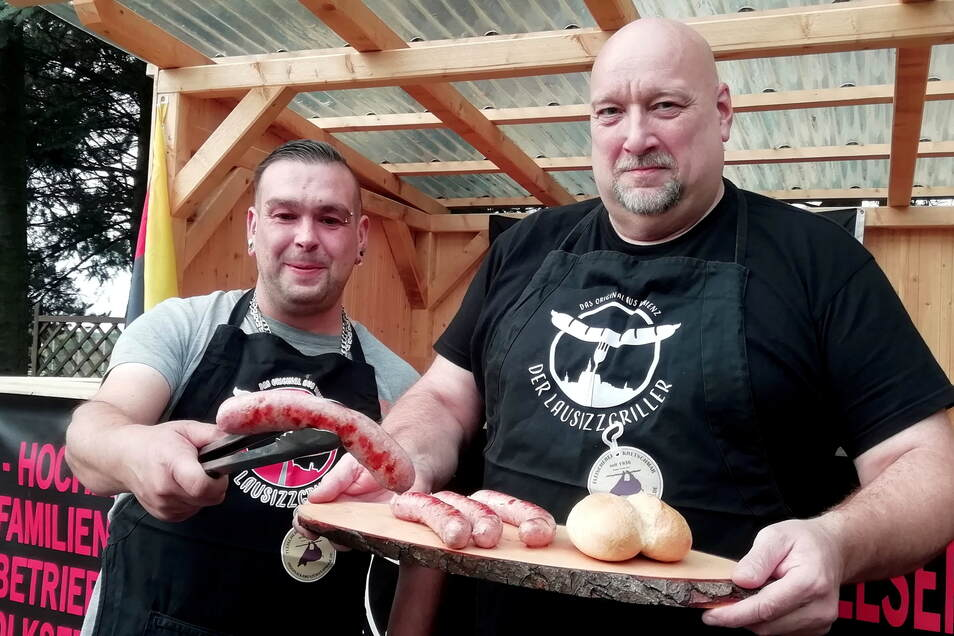 """Grillexperte Manuel Terne (l.) und sein Kompagnon Thomas Wolf haben den Grill im Kamenzer Stadion angeworfen. Dort bruzzeln schon die neuen """"Lausizzknacker""""."""
