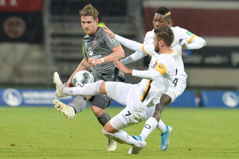 Oliver Sorg (l) von Nürnberg spielt gegen Niklas Kreuzer und Moussa Kone von Dresden.