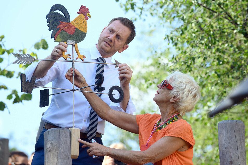"""Zur Einweihung des Traumzaubergartens kamen am Mittwoch Ministerpräsident Michael Kretschmer und Autorin Monika Ehrhardt-Lakomy nach Bautzen. Gemeinsam installierten sie den Wetterhahn """"Ritter Adalbert""""."""
