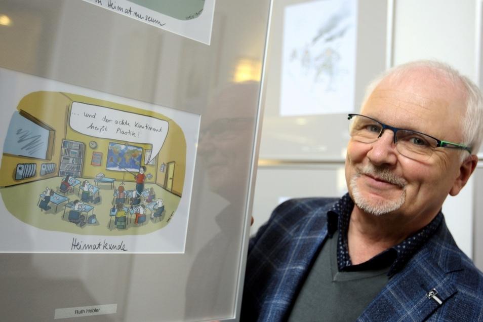 Der Pirnaer Herrenausstatter und Schneidermeister Eckhard Gnauk schaut sich eine von 80 Karikaturen in der Hauptstelle der Volksbank Pirna an und muss schmunzeln: … und der achte Kontinent heißt Plastik! … heißt es da in Heimatkunde.