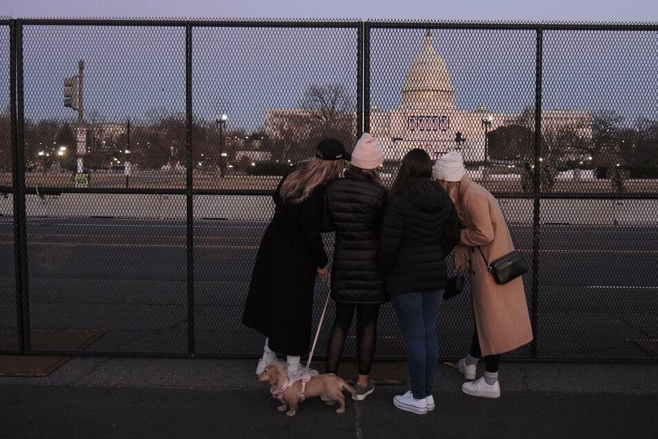 USA, Washington: Passantinnen stehen vor einem Sicherheitszaun und blicken in Richtung Kapitol.