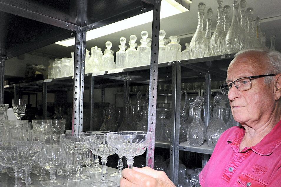 """Jochen Exner, Gründervater und ehemaliger Chef des Glasmuseums Weißwasser, stöbert im Fundus """"100 Jahre Bärenhütte Weißwasser"""". So manche Rarität konnte er für die Nachwelt sichern – als stumme Zeugen der Geschichte der Glasindustrie in der"""