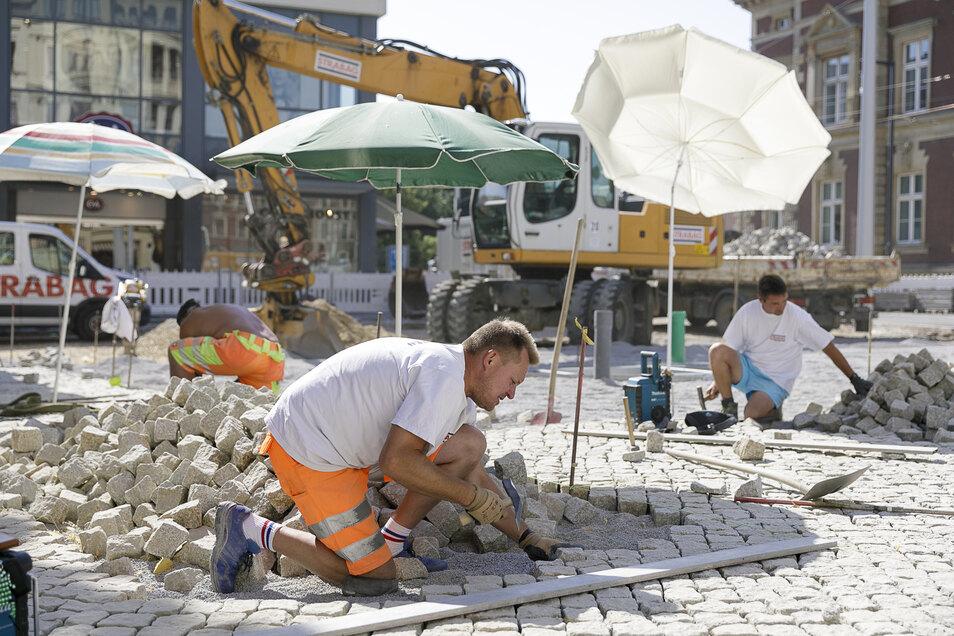 Unter Sonnenschirmen: Arbeiter der Firma Strabag haben voriges Jahr auf dem Görlitzer Postplatz die Pflastersteine verlegt.