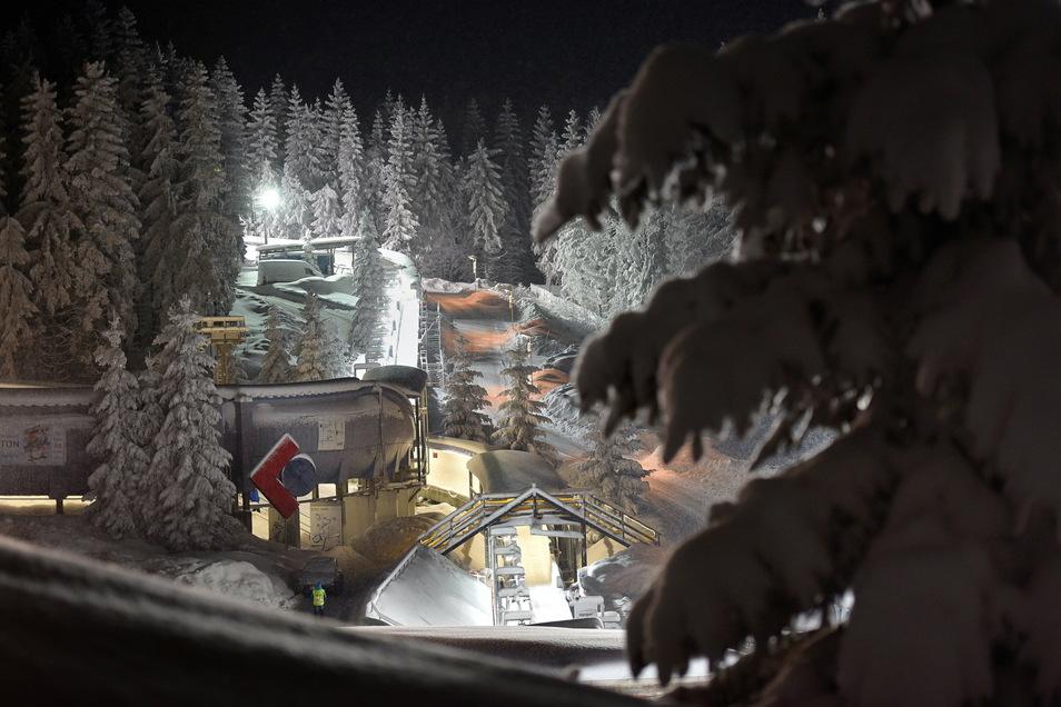 Idylle im Lampenschein: Die Altenberger Bobbahn leuchtet im Winterwald.