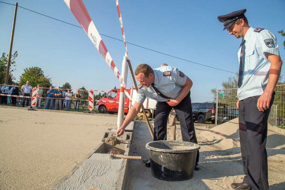 André Bucher, Wehrleiter von Mückenhain, und Sebastian Junge, stellvertretender Wehrleiter von Särichen, bei der Grundsteinlegung für das neue Feuerwehrgerätehaus in Särichen.