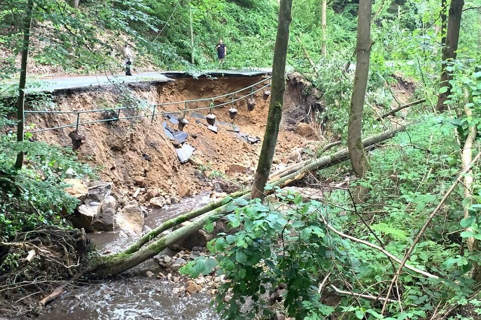 Der Hang wurde ausgespült, der Asphalt weggerissen. Der Hirschgrund in Reinhardtsdorf-Schöna ist unpassierbar.