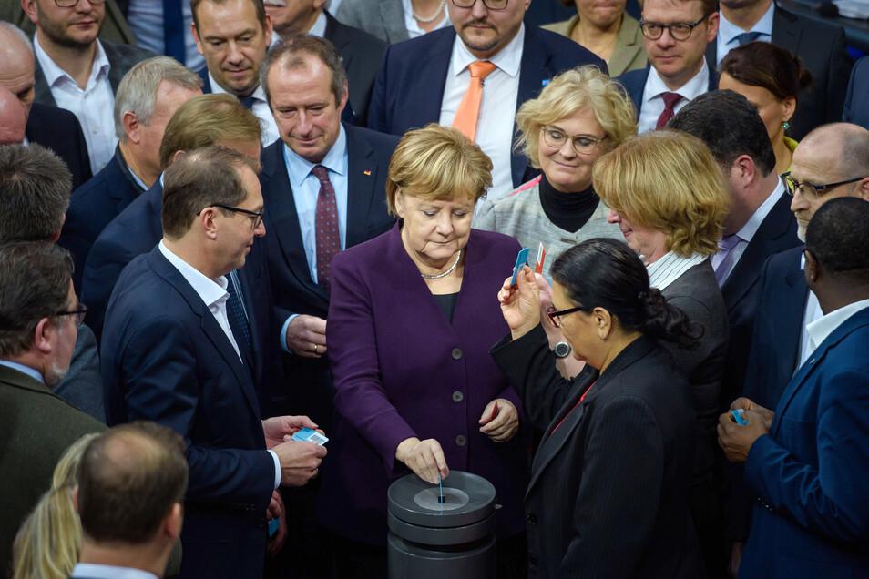 Bundeskanzlerin Angela Merkel (CDU) gibt am Freitag gemeinsam mit anderen Abgeordneten ihre Stimmkarte zum Haushalt 2020 ab.