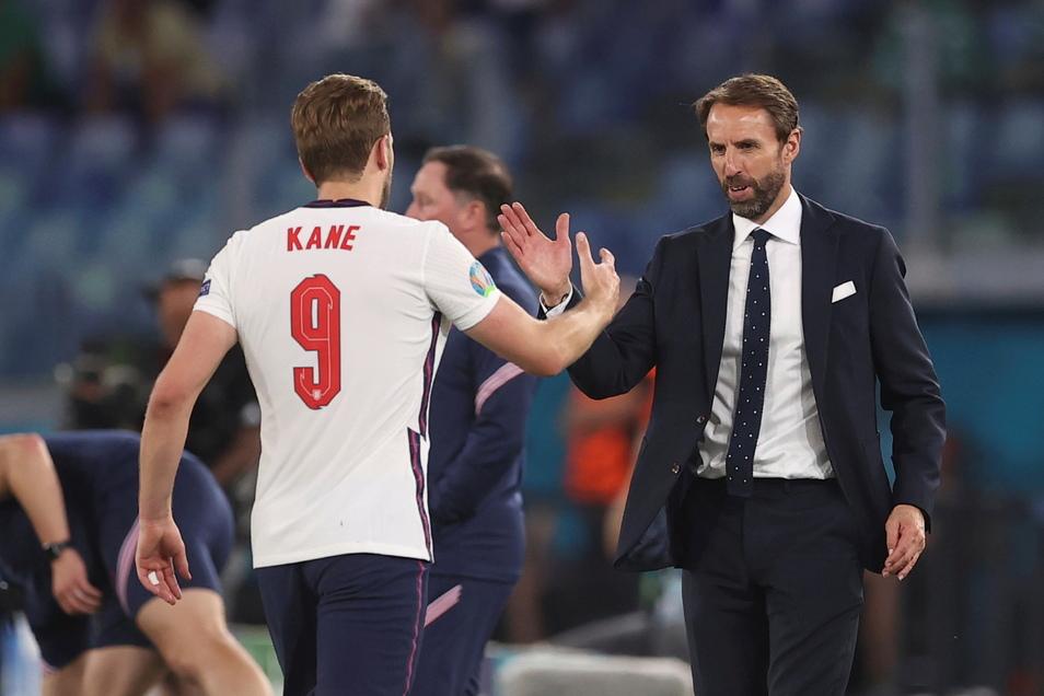 Englands Nationaltrainer Gareth Southgate (r) bedankt sich während der Partie gegen die Ukraine beim ausgewechseltem Harry Kane.