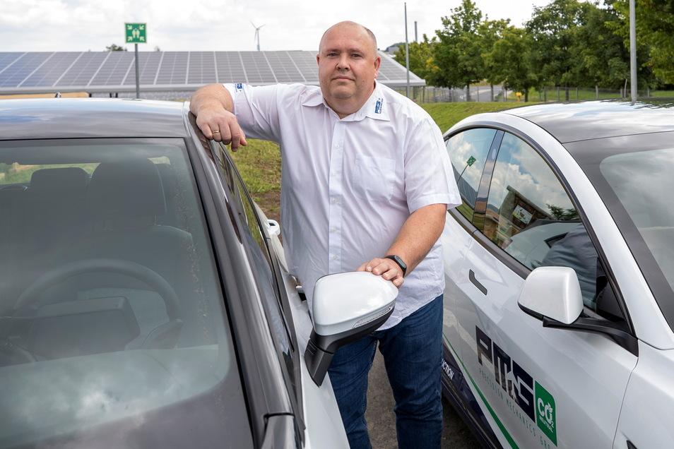 Mitarbeiter René Nowak von der PMG Precision Mechanics Group aus Wilsdruff steht vor einem VW ID4, der zu der Fahrzeugflotte mit dem E-Motor gehört.