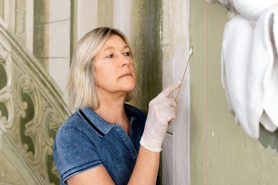 Restauratorin Martina Oeter untersucht eine Wand im Treppenhaus des Rammenauer Barockschlosses. Zurzeit nehmen die Fachleute Farbproben, die im Labor untersucht werden. Die um 1800 entstandenen Illusionsmalereien sollen bis Ende 2020 möglichst originalget