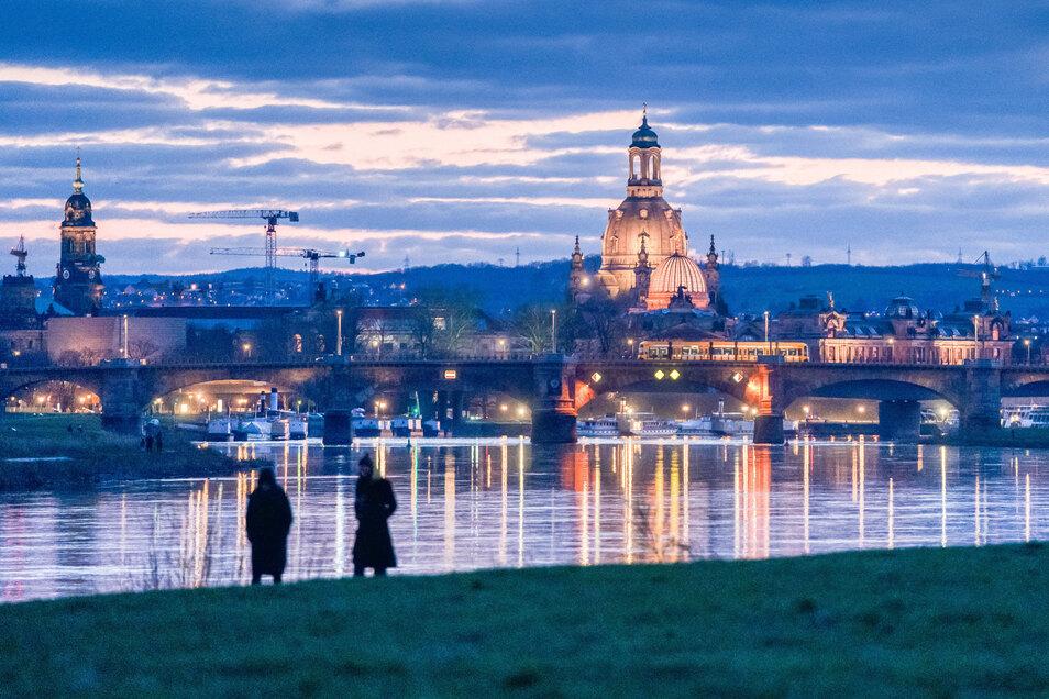 Ziemlich allein: Zwei Personen spazieren an der Elbe in Dresden. So wie bundesweit gelten auch in Sachsen seit Montag strikte Ausgangsregeln.