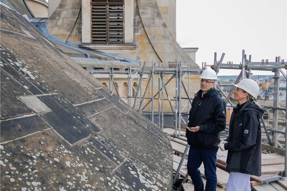 Restauratorin Dana Krause und Bauleiter Thomas Gottschlich inspizieren die Ausblühungen auf dem Choranbau der Frauenkirche.