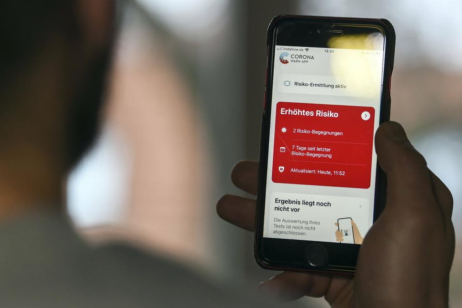 Auf einem Handy zeigt die Corona Warn-App ein erhöhtes Risiko an.