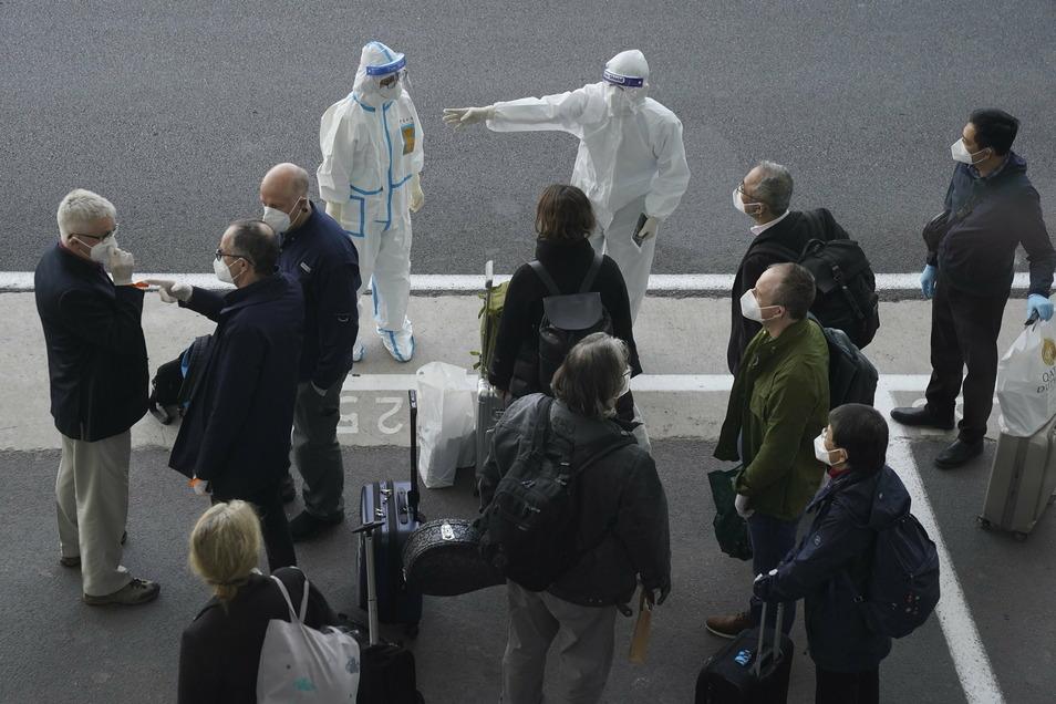 Arbeiter in Schutzkleidung empfangen die Mitglieder eines Teams der Weltgesundheitsorganisation (WHO) am Flughafen in Wuhan.